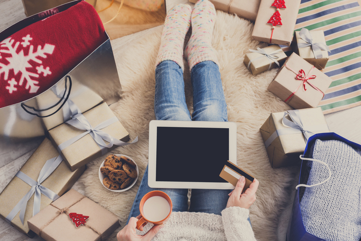 Christmas online shopping top view. Female buyer touch screen of tablet, copy space. Woman drinks milk, buys presents, prepare to xmas eve, among gifts boxes and packages. Winter holidays sales