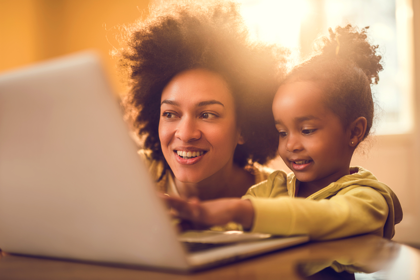 Young smiling African American mother teaching her little daughter how to use laptop at home.